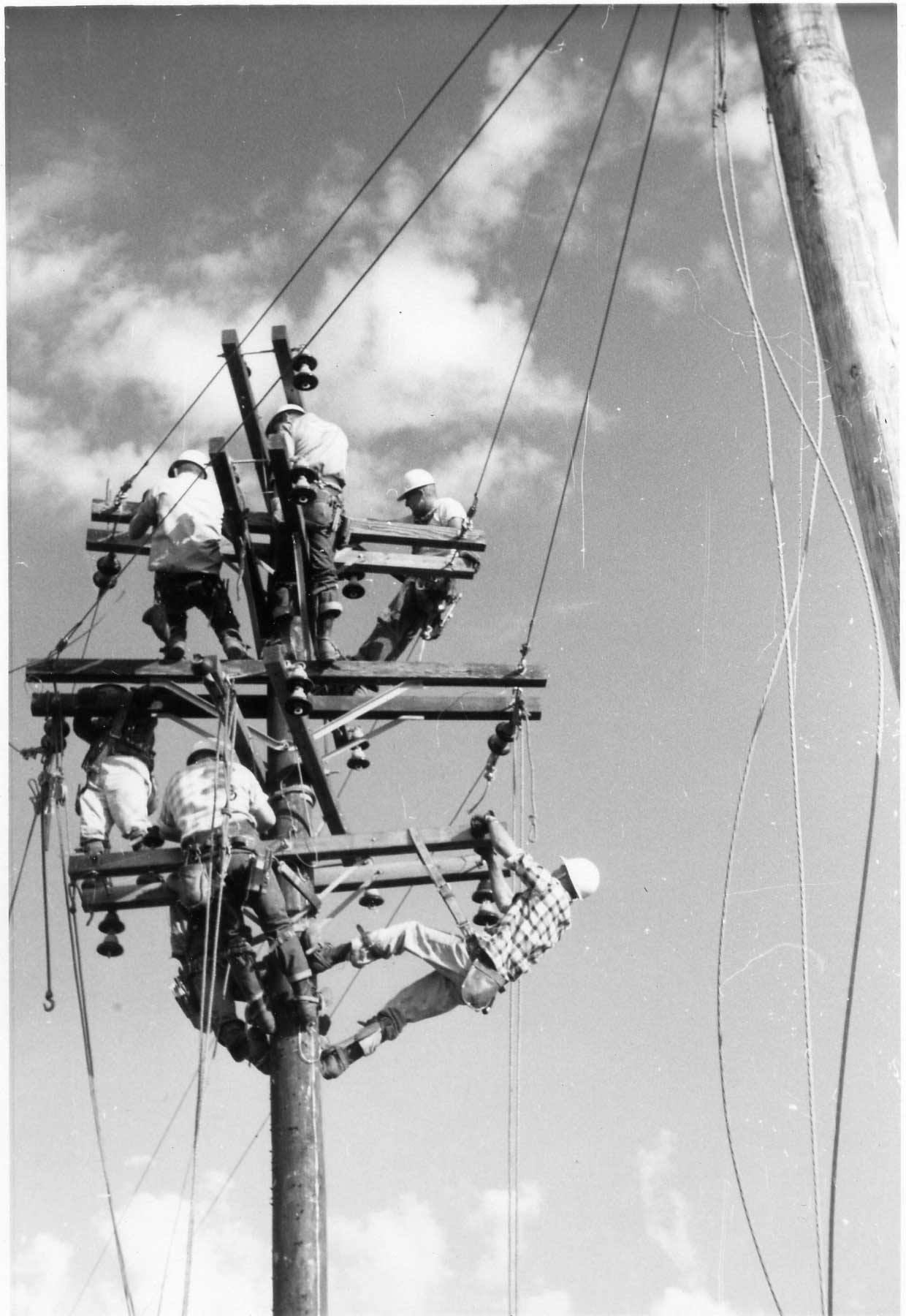 Seven linemen on top of a power pole